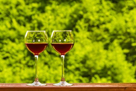 Two glasses of red wine on the deck of a wooden house on a green fresh forest background. Copyspace.