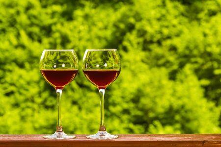 Zwei Gläser Rotwein auf dem Deck eines Holzhauses auf grünem, frischem Waldhintergrund. Exemplar.