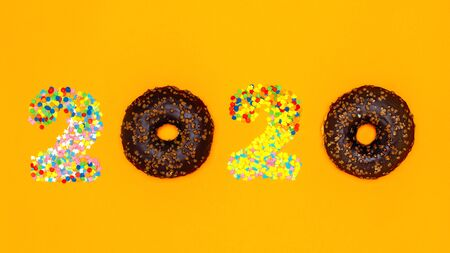 Food concept 2020 made of donuts and confectionery sprinkles. Banner.