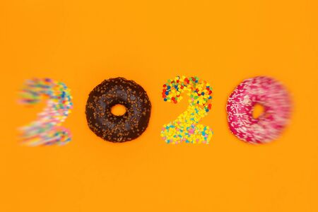 Food concept of approaching the new year 2020 made of donuts and pastry topping.