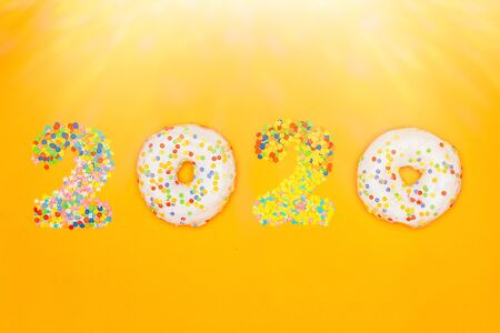 Happy New Year 2020 made of donuts and pastry topping in the sunshine.