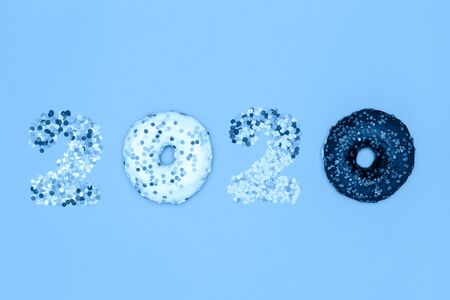 Food concept 2020 made of donuts and confectionery sprinkles and tinted in trending Classic Blue.