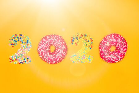 Happy New Year 2020 made of donuts and confectionery topping in sunny glare. Banco de Imagens