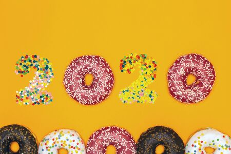 Happy New Year 2020 made of donuts and pastry topping. Copy space. Banco de Imagens