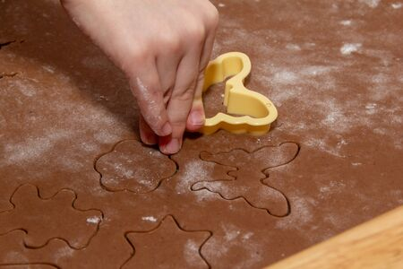 Cutting figures from the dough using special stencils for making ginger Christmas cookies. Children's hands close-up. Home, family prepare for the holidays concept. Stock Photo