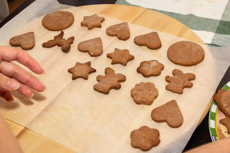 Baking holiday cookies. Womans hands lay ready-made baking for decoration. Christmas and New Year. Stock Photo