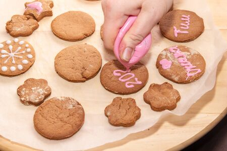 Baking holiday cookies. Hands decorating gingerbread. Christ. Mas and new year.