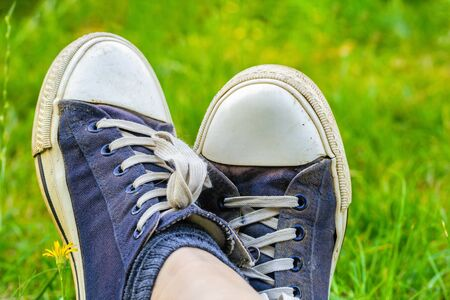Legs in old, dirty, shabby sneakers on the green grass. Tourist and travel concept. 스톡 콘텐츠
