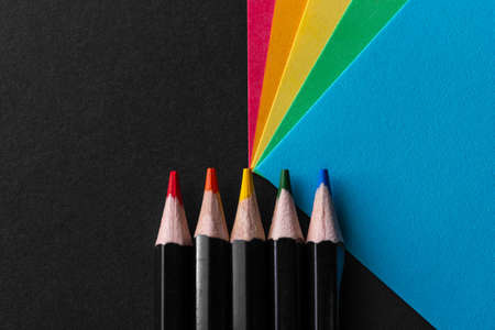 Colored rainbow paper corners and Black wooden colored pencil set on black textured background. Business concept. Layout for design. Copy space. High quality photo Imagens