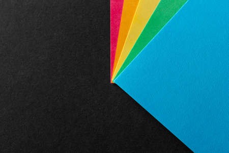 Colored rainbow paper corners on black textured background. Business concept. Layout for design. Copy space. High quality photo