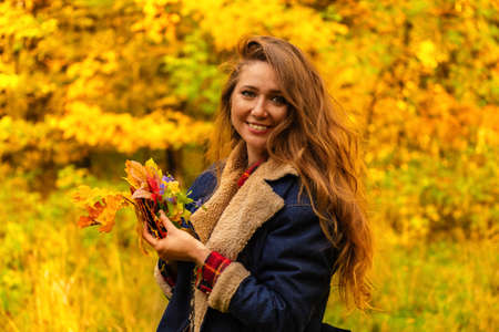 Autumn mood. Young red-haired woman in autumn forest smiles and holds fall foliage. High quality photo Imagens
