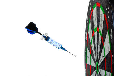 A disposable syringe in the form of a dart with the inscription Vaccine flies into a dartboard target, isolated on a white background. Coronavirus vaccine concept. High quality photo