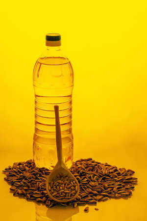 Sunflower oil in plastic bottle and seeds on yellow background. High quality photo Imagens
