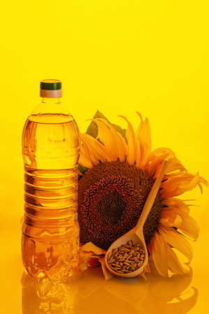 Sunflower oil in plastic bottle, seeds and flower on yellow background. High quality photo Imagens
