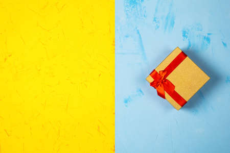 Colored square gift box on concrete background, flat lay, top view