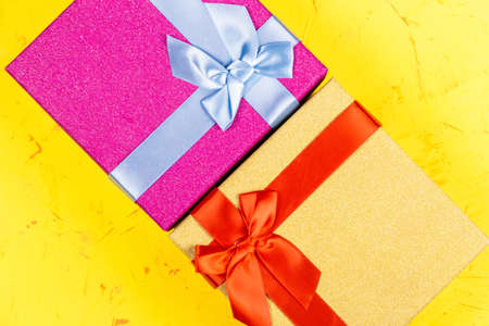 Colored square gift boxes on concrete background, flat lay, top view.