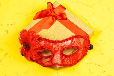 Colored square gift box on concrete background and red carnival mask, flat lay, top view.