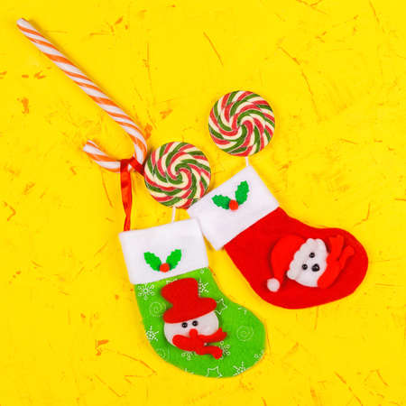 Christmas and New Years concept. Christmas Socks and lollipops and candy kane on a yellow concrete background. Top view, copy space. Imagens