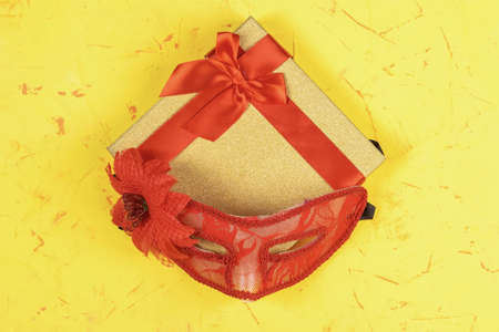 Colored square gift box on concrete background and red carnival mask, flat lay, top view