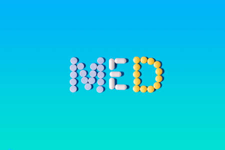 Medical concept. The word MED made from pills of different shapes and colors on a gradient blue and green background. Use for cover, banner, blog Imagens