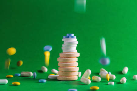 Stacks of pills of various sizes and colors on green