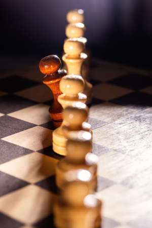 Black pawn in a row of whites on a chessboard. Out of the ordinary concept