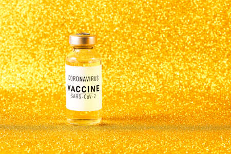Coronavirus vaccine. Vaccine values during the acute period of the covid-19 pandemic concept. Vial on a golden background. Gold toning Imagens
