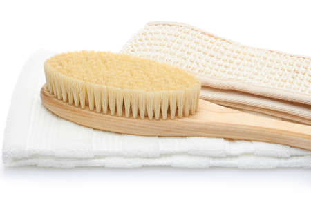 A dry massage brush, a washcloth made of natural materials and a cotton towel on a white background. Cleanliness and body care concept