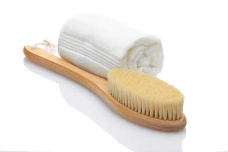 A dry massage brush made of natural materials and a cotton towel on a white background. Cleanliness and body care concept 版權商用圖片