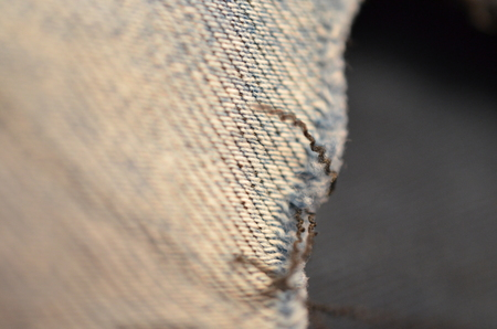 blue texture maden from a piece of jeans with torned hole with threads blurred toned