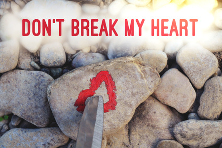 Cutting knife diving pink heart painted with lipstick on piece of stone. Symbol of the end of love and of two people break up and divorce with text letter Don't break my heart