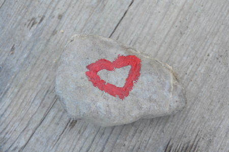 Pink heart painted with lipstick on piece of stone on background of wooden board