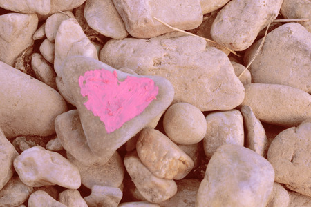 Pink heart painted with lipstick on piece of stone on background of many small stones