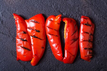 red grilled peppers on black stone . Stock Photo