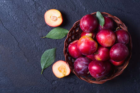 plums in basket on a dark stone background . Stock Photo