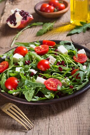 Fresh spring salad with rucola , feta cheese , tomatoes and pomegranate seeds