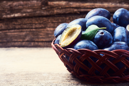 plums in basket on a wooden background .