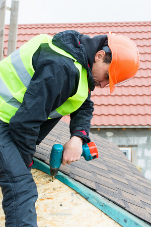 tejas: Roofer builder worker dismantling roof shingles
