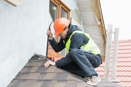 roofer: Roofer builder worker dismantling roof shingles