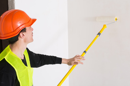 Man smoothing the wallpaper on the wall with a roller