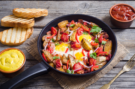 Fried egg with bacon , potato and vegetables