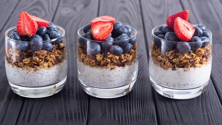 Chia yogurt with granola and berries  ( blueberries , strawberry ) in glass Stock Photo