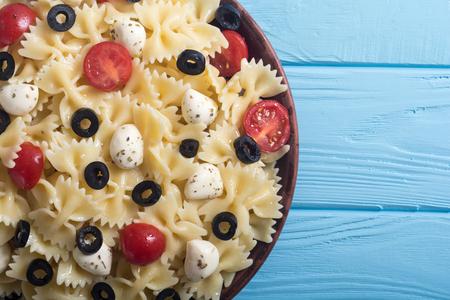 Pasta salad with mozzarella , olives and tomatoes . Italian food background Stock Photo