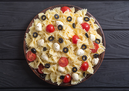 Pasta salad with mozzarella , olives and tomatoes . Italian food background Stock Photo