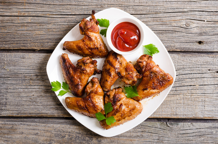 Grilled chicken wings with sauce , tomato and parsley