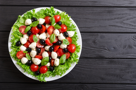 Salad with basil , tomatoes , olives and mozzarella . Italian food Stock Photo