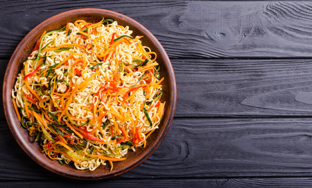 Asian noodles salad in bowl on rustic background