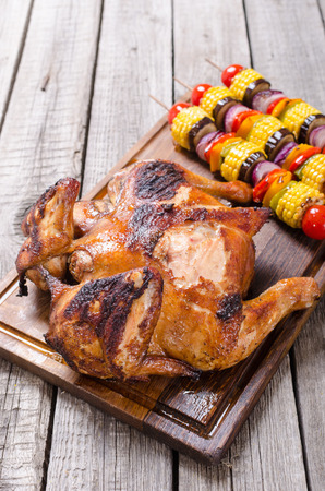 Grilled chicken and vegetables on rustic background