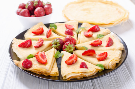 Homemade Russians pancakes with strawberry on rustic background