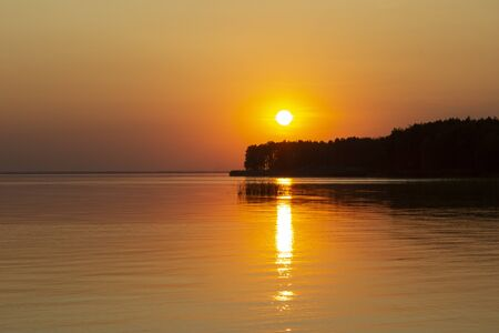 The  horizontal photo of golden sunset above the river or sea. Reflection in the water like fire. Seacoast. 免版税图像